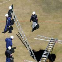 Hidden danger: Police investigate a sinkhole on a fairway at Le Petaw golf course in Hokkaido on Friday after a woman suddenly disappeared into it and drowned during play. | KYODO PHOTO