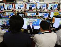 Ratings boost: People at a home electronics retailer in Tokyo's Akihabara district follow news reports about North Korea's rocket launch Sunday. | KYODO PHOTO
