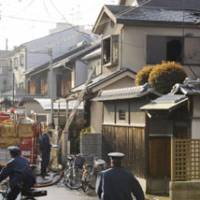 Aftermath: A firefighter investigates in the wake of an early Monday house fire in Osaka. | KYODO PHOTO