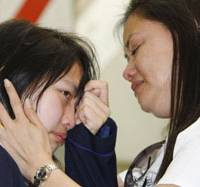 No words: Noriko Calderon wipes away tears as her mother, Sarah, tries to console her at Narita International Airport ahead of her parents' departure for the Philippines on Monday.   KYODO PHOTO