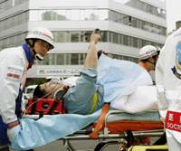 It came from there: A man points skyward as he is carried to an ambulance Tuesday after being injured by a falling pile driver at a construction site in Tokyo's Kojimachi business district. | KYODO PHOTO
