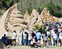 Look but don't touch: People admire sand sculptures based on fairy tales from around the world at the Tottori Sand Dune on Saturday after the World Sand Sculpture Festival kicked off in Tottori. | KYODO PHOTO