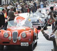 A three-day Jag: A woman on a classic Jaguar roadster waves as a three-day rally across five prefectures in the Kansai region starts Sunday in Osaka's Umeda district. | KYODO PHOTO