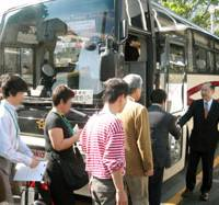 Magical ministry tour: A Ministry of Economy, Trade and Industry official welcomes job seekers to a ministry-organized bus tour in Chiyoda Ward, Tokyo, on Wednesday. | KYODO PHOTO
