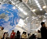 Hopes in the air: Visitors watch pieces of paper bearing eco-friendly messages fly around inside a giant balloon Thursday during a preview of the 150th Anniversary of the Opening of the Port of Yokohama exposition. | SATOKO KAWASAKI PHOTO