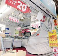 Closed for business: A woman surveys damage at an Osaka jewelry shop Friday after burglars earlier that day used a truck to smash through the shop's shutters. | KYODO PHOTO