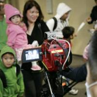 Welcome to Japan: A family arriving from Mexico is checked out with a thermographic device at Narita airport in Chiba Prefecture on Saturday.   KYODO PHOTO