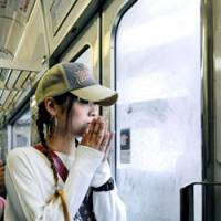 In remembrance: A woman offers a moment of silence inside a JR Fukuchiyama Line train as it passes the site of the deadly 2005 derailment that killed 107 people in Amagasaki, Hyogo Prefecture, on Saturday. | KYODO PHOTO