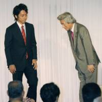 Hereditary handoff: Ex-Prime Minister Junichiro Koizumi bows to his son, Shinjiro, during a meeting in Yokosuka, Kanagawa Prefecture, on Sept. 27 during which he formally announced his plan to retire and pass the torch to his son. | KYODO PHOTO