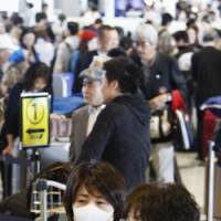 In the know: People wearing masks wait Tuesday in a departure lobby at Narita International Airport in Chiba Prefecture after the World Health Organization raised its flu pandemic alert level to Phase 4.   KYODO PHOTO