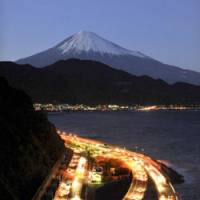 Mountain path: Vehicles on Sunday stream along a section of the Tomei Expressway in Shizuoka Prefecture, with a twilit Mount Fuji in the background. | BLOOMBERG