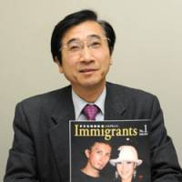 Spread the word: Immigrants magazine editor in chief Susumu Ishihara holds up a copy of the first edition in Minato Ward, Tokyo, on April 7. Ishihara is also president of the Japan Immigrant Information Agency. | SATOKO KAWSAKI PHOTO