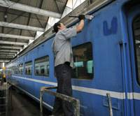 Fresh coat: A Blue Train car is repainted at State Railway of Thailand's maintenance facility in central Bangkok in February. | KYODO PHOTO