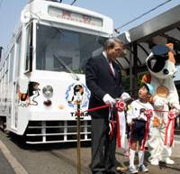 Cat-alyst: An Okayama Electric Tramway Co. official cuts a ribbon Thursday with kindergartner Katsuki Nakashima in front of a new tram decorated with illustrations of Tama, the cat 'stationmaster' of Kishi Station in Wakayama Prefecture. | KYODO PHOTO
