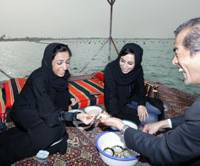 Pearl production: Daiji Imura, a pearl dealer-turned-pearl producer, shows two women pearls plucked from oysters on a raft in the emirate of Ras Al Khaimah in the United Arab Emirates on Feb. 17. | KYODO PHOTO