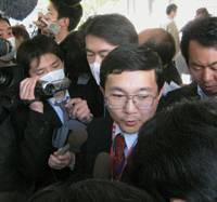 Center of attention: A spokesman for Yokohama Municipal Citizen's Hospital is surrounded by reporters Friday after a high school boy from Yokohama returned from Canada and tested positive in a preliminary A-type flu test. | KYODO PHOTO