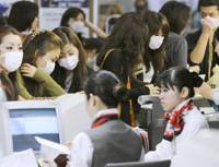 Just in case: Travelers wearing masks check in at a counter at Kansai International Airport on Saturday. | KYODO PHOTO