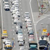 Aftermath: A disabled car is readied to be towed away Sunday afternoon on the Meishin Expressway in Kyoto Prefecture after a five-vehicle collision. | KYODO PHOTO