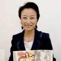 Page turner: Kaori Kitsuda, who heads personnel agency Frajouterie Co., holds up a copy of 'manga' comic Hello Work at the Age of 40 during a recent interview at the firm's office in Tokyo's Akasaka district. | YOSHIAKI MIURA PHOTO