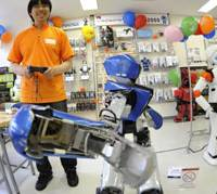 Ducking and diving: Hideki Idaka, manager of newly opened Vstone Robot Center in Tokyo's Akihabara district, uses a remote control to make Alcnon?, a 1.3-meter-tall robot, throw a punch Monday.   AP PHOTO