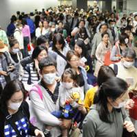 Checkup: Passengers pack the quarantine section at Narita International Airport on Tuesday as people started coming back from overseas trips for Golden Week. | KYODO PHOTO