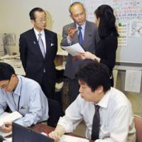 Manning battle stations: Chief Cabinet Secretary Takeo Kawamura and Health, Labor and Welfare Minister Yoichi Masuzoe speak with workers at a phone-consultation center set up for influenza-related inquiries. | KYODO PHOTO
