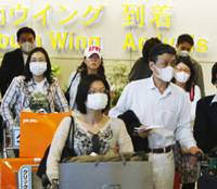 Full protection: Face masks are ubiquitous at Narita International Airport as travels return from Golden Week vacations. | KYODO PHOTO