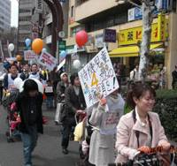 Taking it to the streets: Scores of people push baby strollers through the streets of Shibuya Ward, Tokyo, on April 5 in a march organized by nonprofit Fathering Japan to demand better day care facilities for preschoolers.   FATHERING JAPAN PHOTO