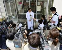 Briefing: A medical official talks to reporters Sunday outside a Chiba hospital where a swine flu patient is being treated. | KYODO PHOTO