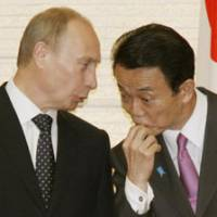 Eye to eye: Prime Minister Taro Aso and his Russian counterpart, Vladimir Putin, chat during a signing ceremony for a bilateral pact Tuesday night in Tokyo.   KYODO PHOTO