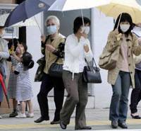 Just in case: People walk through Kobe wearing protective masks after the nation's first homegrown case of swine flu was confirmed on Saturday. | KYODO PHOTO