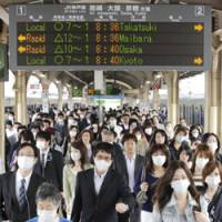 On the go: Commuters in masks rush to work Tuesday morning at JR Sannomiya Station in Kobe.   KYODO PHOTO