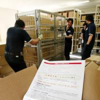 Help is on the way: Workers at Sapporo City Hall on Tuesday move boxes of application forms for the government's cash handout program. | KYODO PHOTO