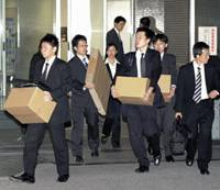 Special delivery: Osaka prosecutors carry boxes of confiscated documents from the head office of Japan Post Service Co. in Tokyo on Tuesday night.   KYODO PHOTO
