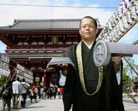 A little off the top: A Buddhist monk at Sensoji Temple in Taito Ward, Tokyo, shows 'kawara' roof tiles made of titanium that now protect the main hall of the landmark temple. | KYODO PHOTO