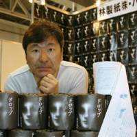 Pulp fiction: Writer Koji Suzuki poses with rolls of toilet paper on which his short horror story 'Drop' is printed, at a printing factory in Fuji, Shizuoka Prefecture, on Saturday. | KYODO PHOTO
