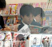 Reading for pleasure: Salarymen read comic books at a convenience store in the Shibaura district of Minato Ward, Tokyo. | YOSHIAKI MIURA PHOTO