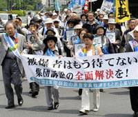 Survival instinct: About 150 atomic bomb survivors and their supporters march along a street in Chiyoda Ward, Tokyo, on Tuesday to demand that the government grant all survivors of the blasts lower medical costs and allowances when being treated for radiation-related illnesses. | KYODO PHOTO