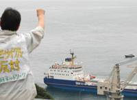 Fight the power: A man protests Wednesday against the arrival of a cargo ship carrying recycled nuclear fuel at Shikoku Electric Power Co.'s Ikata plant in Ehime Prefecture. | KYODO PHOTO