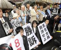 Victory: Plaintiffs seeking official recognition as atomic bomb victims hold victory banners and photographs of their deceased comrades with supporters outside the Tokyo High Court on Thursday. | KYODO PHOTO