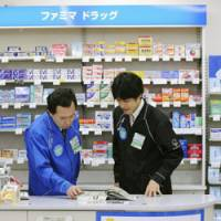 Uncharted territory: A pharmacist (left) hands instructions for a nonprescription drug to a sales clerk at a FamilyMart convenience store in Chiyoda Ward, Tokyo, on Friday. | KYODO PHOTO