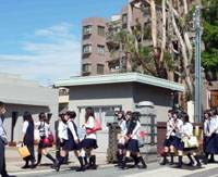Back to the grind: Students enter Hyogo High School in Nagata Ward, Kobe, on Saturday morning following a two-week shutdown caused by the H1N1 swine flu outbreak. | KYODO PHOTO