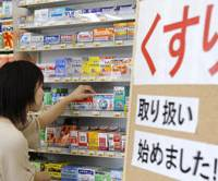 No pharmacist needed: A customer checks packs of nonprescription drugs Monday at a Seven-Eleven in Chiyoda Ward, Tokyo. | KYODO PHOTO