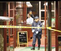 Gas fatality: An investigator walks through the entrance at the Yamaguchi Shuhou Plaza Hotel in Yamaguchi's Akiyoshi district Wednesday. A photographer was killed and another 21 people sickened by carbon monoxide poisoning in the inn Tuesday. | KYODO PHOTO