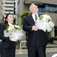 Remembering: John Bundy, president of Schindler Elevator K.K., prepares to offer flowers Wednesday at a Minato Ward, Tokyo, apartment complex where one of the company's elevators killed a teenage boy three years ago. | KYODO PHOTO