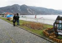 Ghost town: Only a handful of tourists walk along the shore of Lake Toya last December. | KYODO PHOTO
