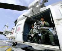 Noisemakers: Maritime Self-Defense Force crewmen man a machinegun and acoustic device on a helicopter aboard the destroyer Sazanami in the Gulf of Aden on Saturday. The Long Range Acoustic Device can announce the chopper's presence in a bid to ward off pirates. | KYODO PHOTO