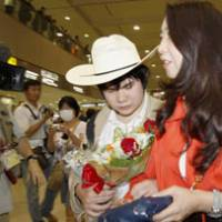 Tickled the ivory: Blind pianist Nobuyuki Tsujii arrives at Narita airport on June 9, accompanied by his mother.   KYODO PHOTO