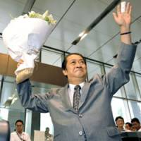 Parting bouquet: Kunio Hatoyama, who resigned last week as internal affairs and communications minister, leaves the ministry Monday as officials see him off. | KYODO PHOTO