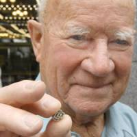 Not to badger: Ex-Australian POW Joseph Coombs holds up an Aso Corp. lapel pin Thursday in Tokyo that the firm gave him when he visited its Fukuoka base. | YOSHIAKI MIURA PHOTO